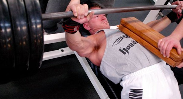 Fitness trainer performing the board press